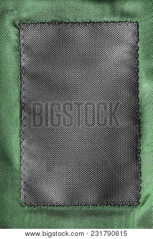 Blank Black Clothes Label On Green Textile Background Closeup