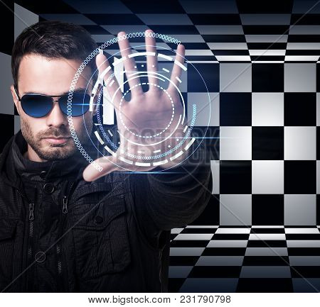 Brutal Man In Sunglasses Controls Virtual System By Hand. Over Chess Background.