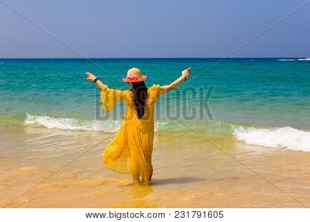 The Girl In The Yellow Dress Is Standing With Her Back To The Camera. Against The Background Of The