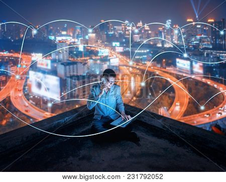Asian Businessman Using Phone And Laptop On Rooftop With Social Connection Lines In Smart City At Ni