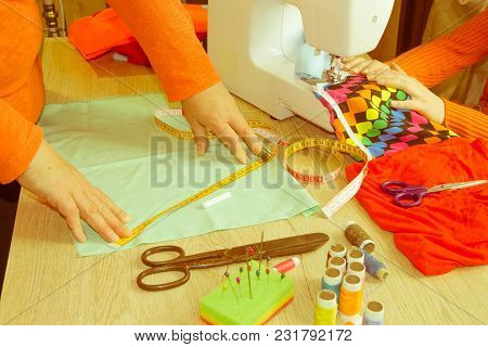 People, Needlework, Sewing And Tailoring Concept - Tailor Woman With Thread In Needle Stitching Fabr