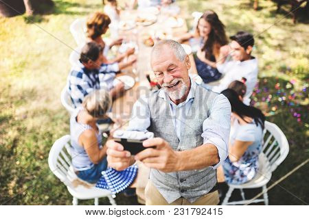 Family Celebration Outside In The Backyard. Big Garden Party. A Senior Man Taking Selfie With A Came