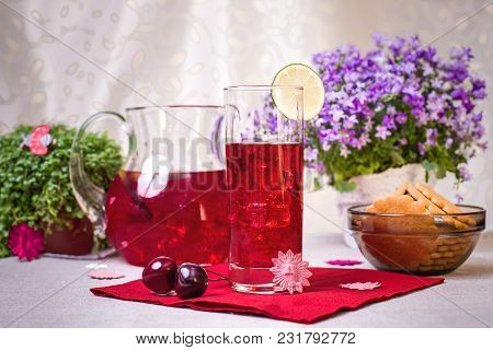 Jug And Glass With Pink Lemonade And Cookie On The Table