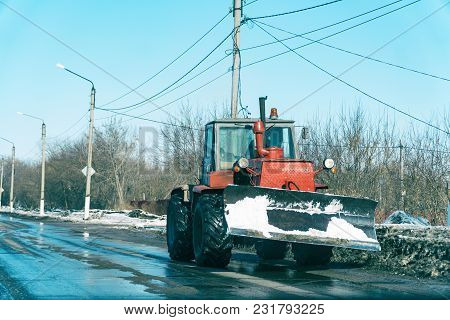 Tractor With Snowplow On The Street Of The City