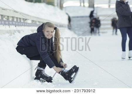 Teenage Longhaired Girl Sitting On Snow Tightening The Laces On The Skates And Smiling, Youth Pastim