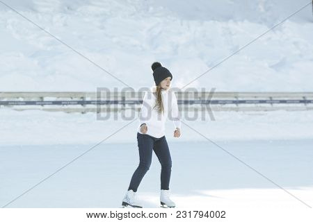 Teen Girl Skating On Outdoor Public Ice Rink, Youth Pastime And Rest