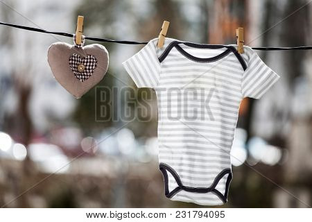 Baby clothes and a brown heart hanging on the clothesline