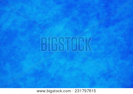 A grainy mottled blue background texture, with clouded effect. Suitable for backgrounds or overlays.