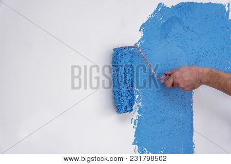 workman painting the wall in blue at house. poster