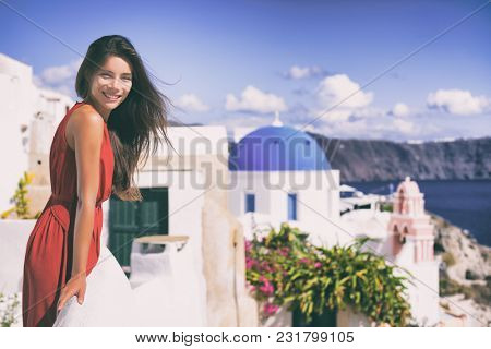 Europe Greece Santorini luxury travel vacation woman on famous santorini Oia island travel european destination. Red dress elegant lady on jet set holidays. Tourist at balcony over blue dome church.