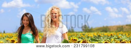 Happy beautiful multiracial woman walking in sunny summer flower field enjoying spring outdoor. Young people lifestyle, two friends laughing banner panorama.