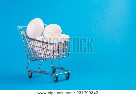 The Cart From A Supermarket Full Of Eggs On A Blue Background. Space For Text. Preparation For Easte
