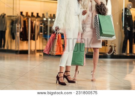 Low Section Of Fashionable Multiethnic Women In Fur Coats Holding Paper Bags And Shopping Together I