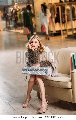 Pensive Young Woman With Shopping Bag Sitting On Armchair And Looking At Camera In Shopping Mall
