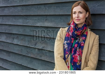 Attractive thoughtful or sad middle aged woman outside