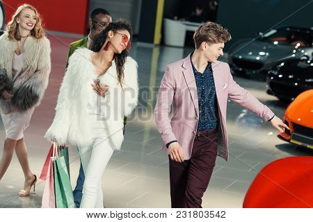 Group Of Young Shoppers Walking By Showroom And Choosing Car