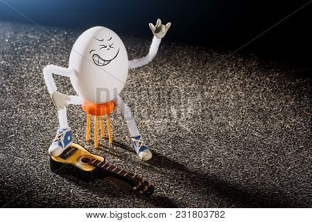Funny Egg Rocker Guitarist Sitting On A Miniature Chair With Guitar On A Stage.