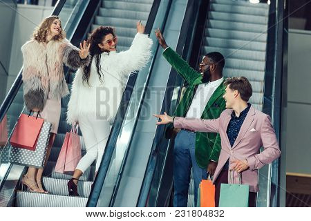 Young Male And Female Shoppers Giving High Five On Escalators At Mall