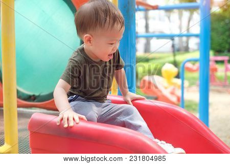 Cute Smiling Little Asian 18 Months / 1 Year Old Toddler Baby Boy Child Playing On A Slide In Playgr
