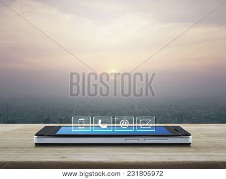 Telephone, Mobile Phone, At And Email Buttons On Modern Smart Phone Screen On Wooden Table Over City
