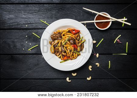Udon Stir Fry Noodles With Meat Or Chicken And Vegetables In A White Plate On Black Wooden Backgroun