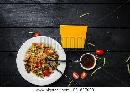 Udon Stir Fry Noodles With Seafood And Vegetables In A White Plate On Black Wooden Background. With