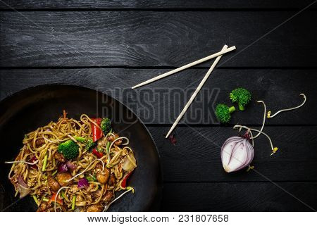 Udon Stir Fry Noodles With Meat Or Chicken And Vegetables In Wok Pan On Black Wooden Background. Wit