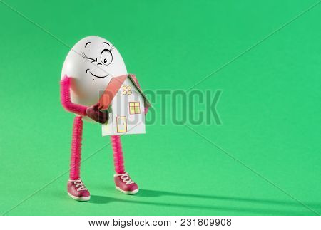 Funny Easter Egg Girl Holding Miniature Paper House Model. Real Estate Agent. Property Insurance, Co