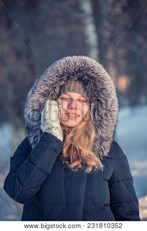 Girl Speaks On The Phone On The Street, In Winter Dressed In A Fur Coat, Frozen Hands