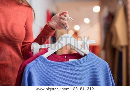 Young girl with clothes in the store