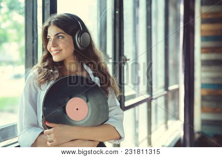 Young woman listen to music on headphones indoors