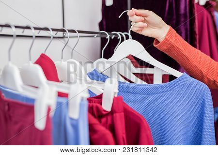 Female hand with a hanger in the store
