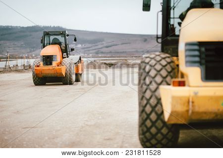 Vibratory Soil Compactor During Road And Highway Construction. Industrial Roadworks With Heavy-duty