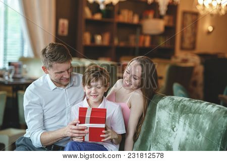 Smiling family with a gift in a restaurant