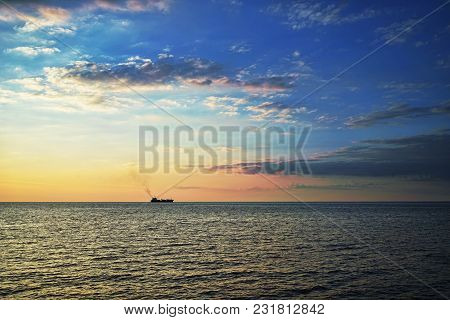 A Lonely Ship On The Horizon In The Sea At Sunset And A Cloudy Sky