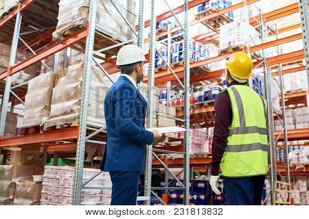 Back View Portrait Of Warehouse Manager And Worker In Hardhats Doing Stock Inventory In Warehouse, L
