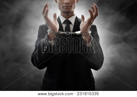 Business Man In Handcuffs On Smoke Background