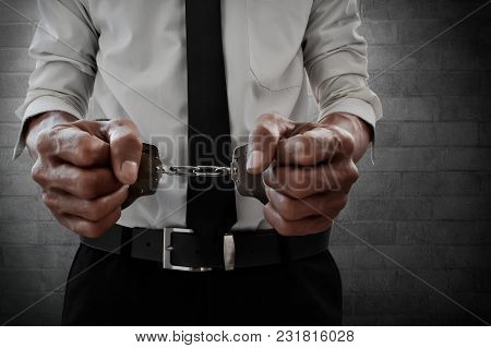 Businessman In Handcuffs On Brick Wall Background