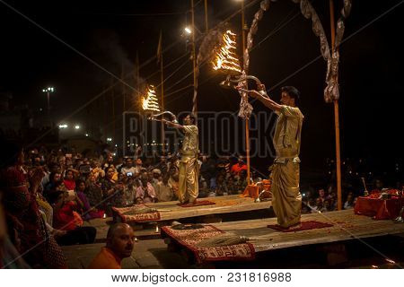 VARANASI, INDIA - MAR 15, 2018: A group of priests perform Agni Pooja (Sanskrit: Worship of Fire) on Dashashwamedh Ghat - main and oldest ghat of Varanasi located on the Ganges.