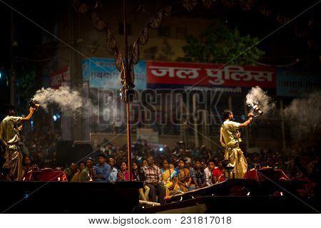 VARANASI, INDIA - MAR 18, 2018: Hindu priests perform Agni Pooja (Sanskrit: Worship of Fire) on Dashashwamedh Ghat - main and oldest ghat of Varanasi located on the Ganges.