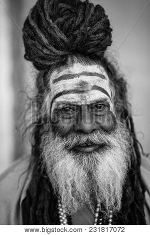 VARANASI, INDIA - MAR 19, 2018: Sadhu or Baba (holy man) on the ghats of Ganges river. Normally a sadhu is a monk, renounced, renounced material enjoyment. In India from 4 to 5 million sadhu.