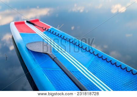 Deck of a racing stand up paddleboard with a paddle and sefety leash.