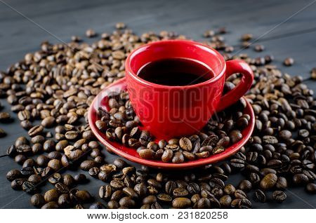 Black Coffee In Red Ceramic Cup And Saucer And Scattered Coffee Grains On Dark Wooden Background. Co