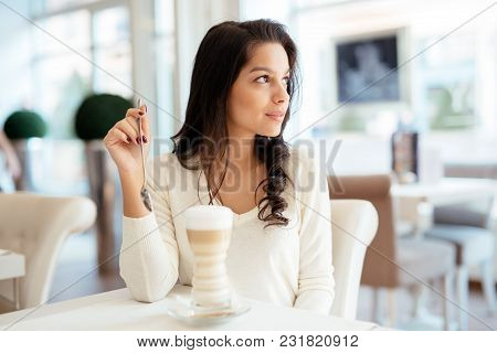 Portrait Of A Beautiful Young Brunette In Cafe Drinking Coffee