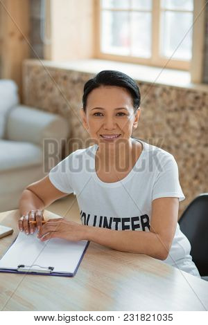 How Help. Top View Of Merry Nice Female Volunteer Sitting At Table While Holding Pencil And Looking