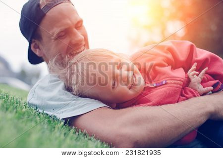 Happy Father Playing With Daughter In The Park At Sunny Day, Intentional Sun Glare