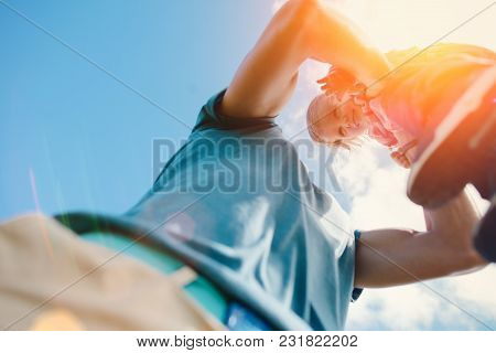 Father Catching And Playing With His Young Baby At Sunny Day, Intentional Sun Glare And Lens Flares