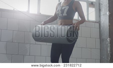 Young Fit And Tone Up Woman Preparing A Fitness Carpet For Abs And Plank Workout