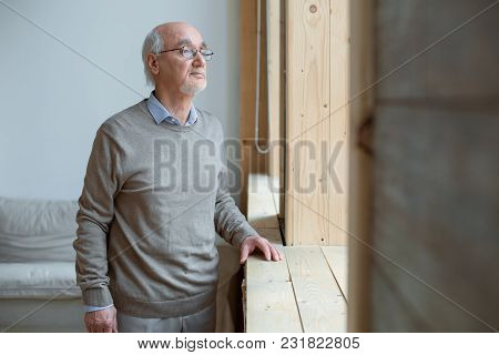Great View. Musing Reflective Senior Man Gazing Through Window While Wearing Glasses And Staying