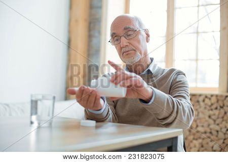Time For Pills. Serious Pleasant Senior Man Sitting At Table While Placing Pills In Hand And Looking